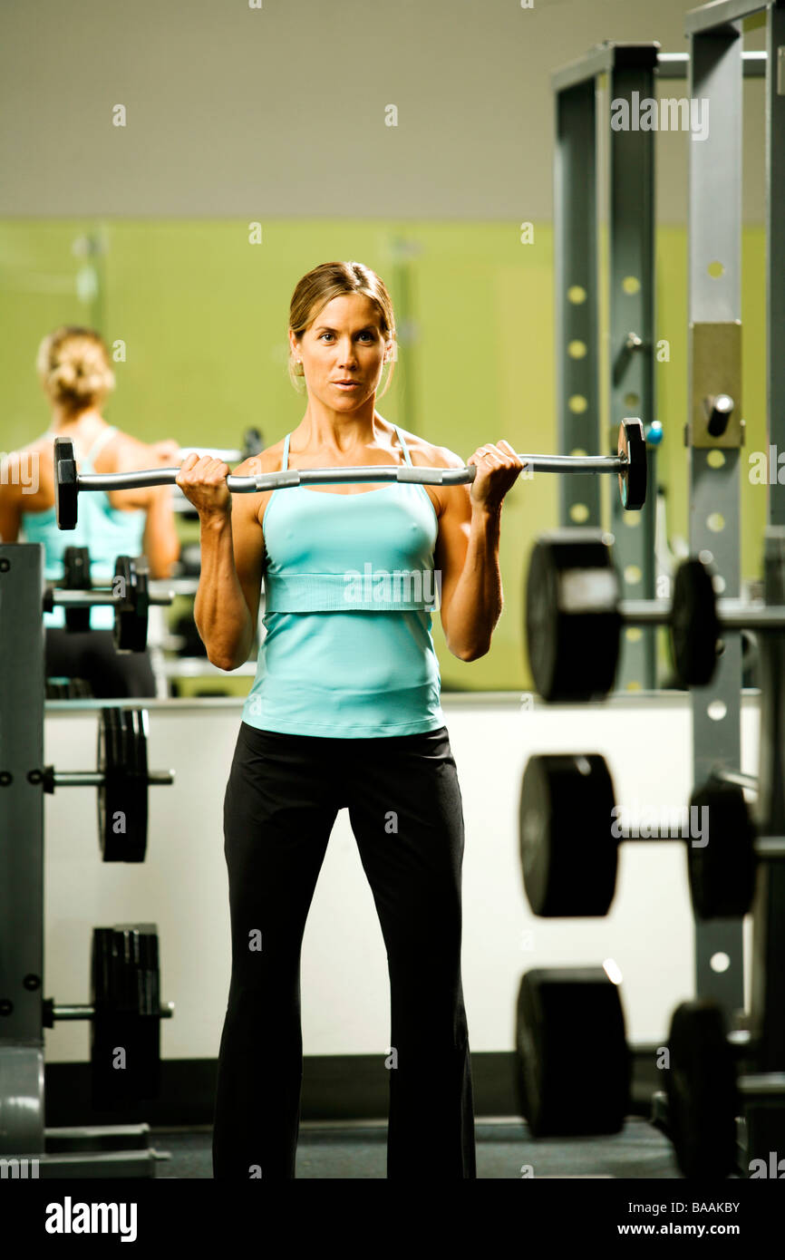 A woman lifting weights in a gym. - Stock Image