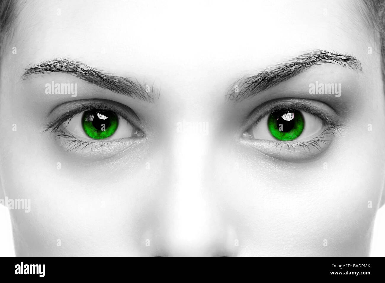 High contrast black white close up of a womans eyes coloured green - Stock Image