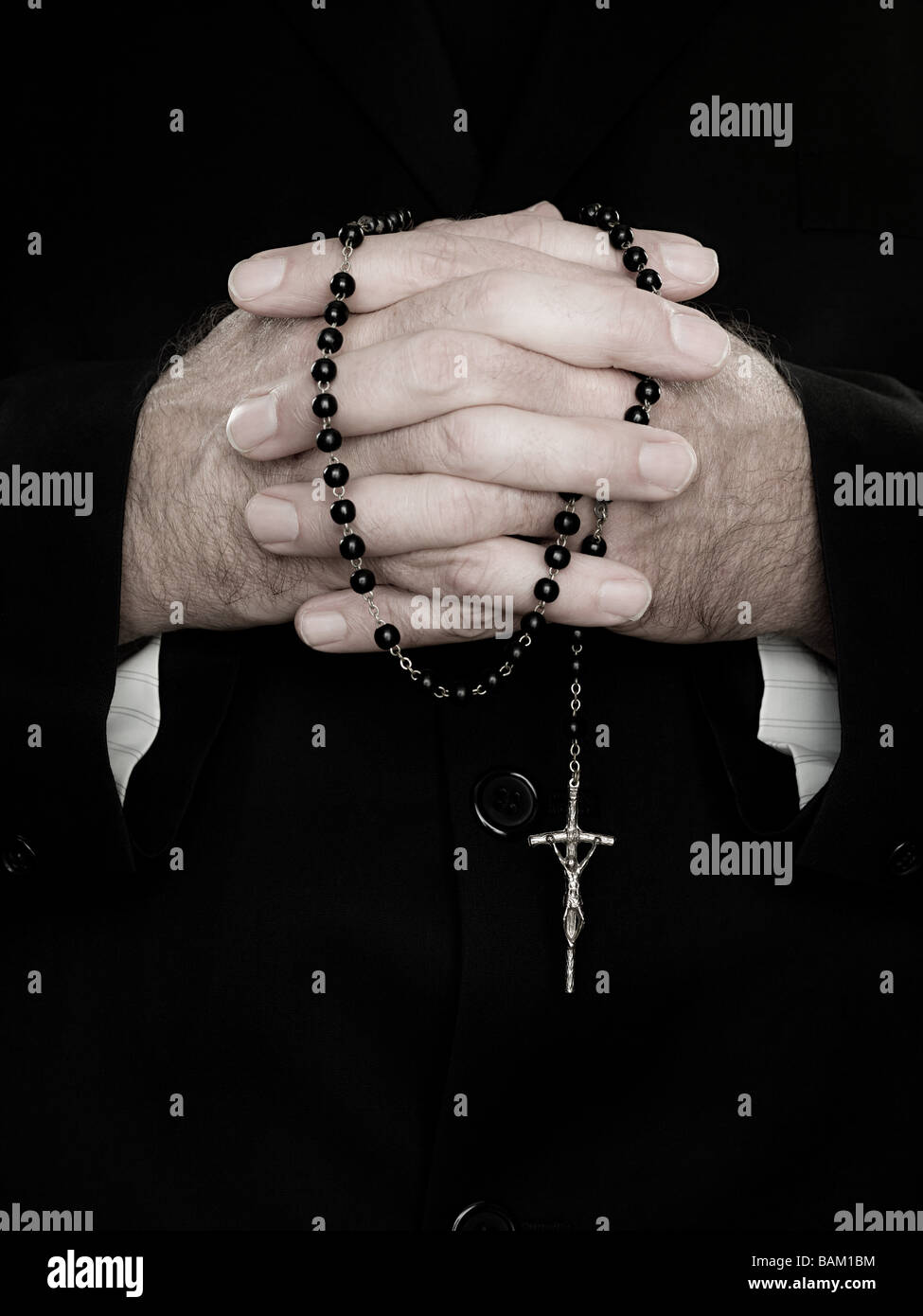 A close up of priest holding prayer beads - Stock Image