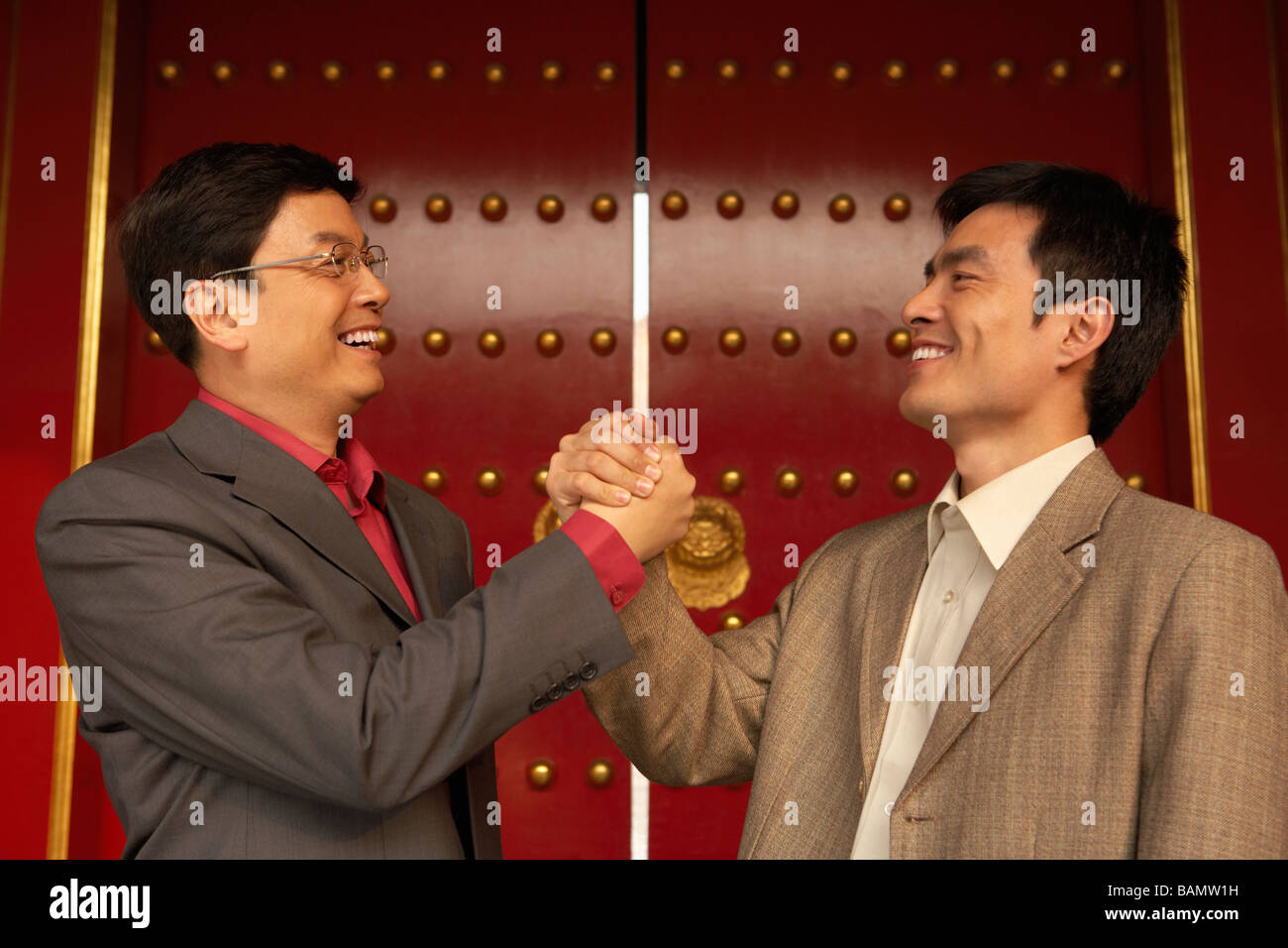 Two Businessmen Shake Hands Outside The Forbidden City - Stock Image