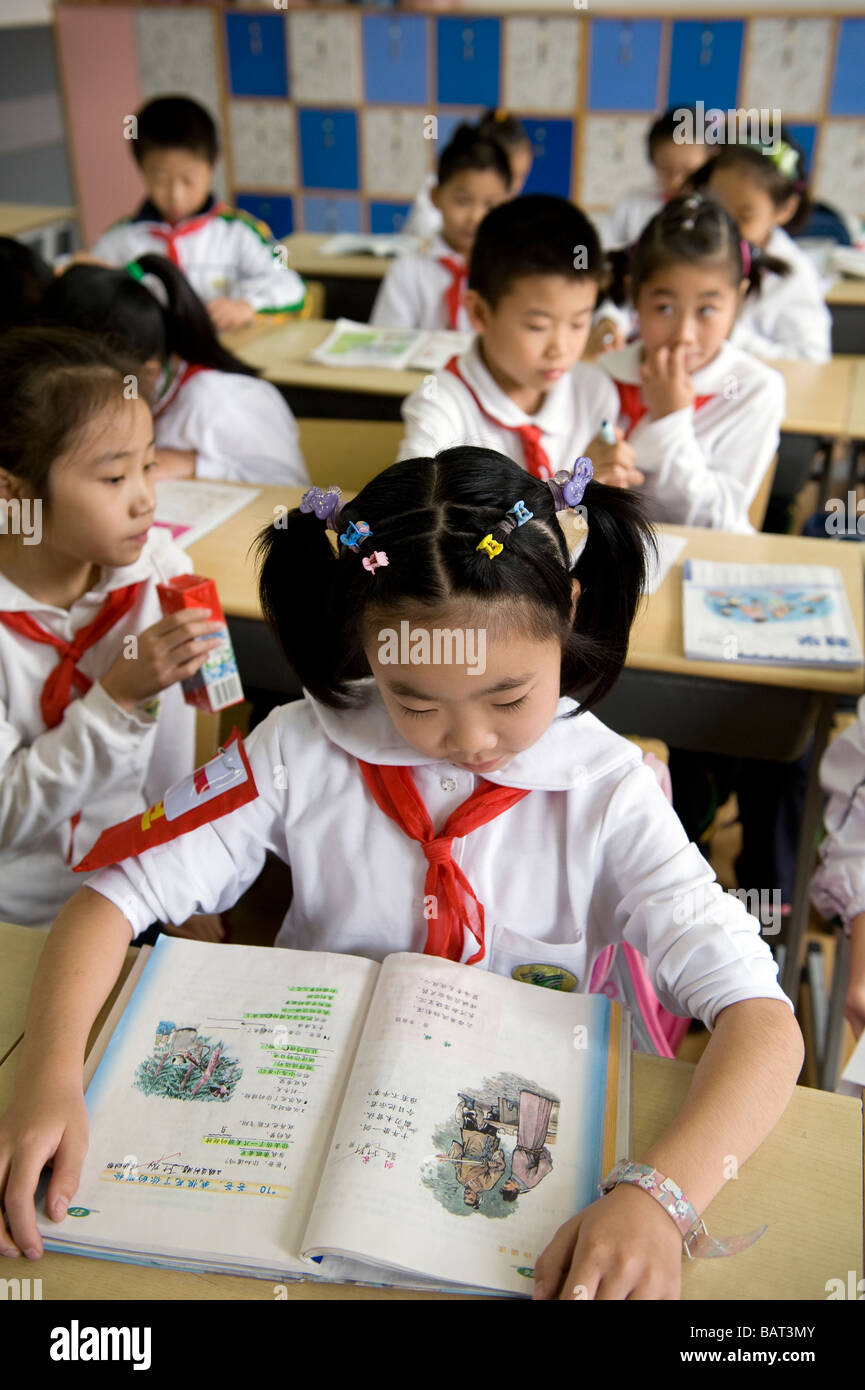 Young students reading from a text book. - Stock Image