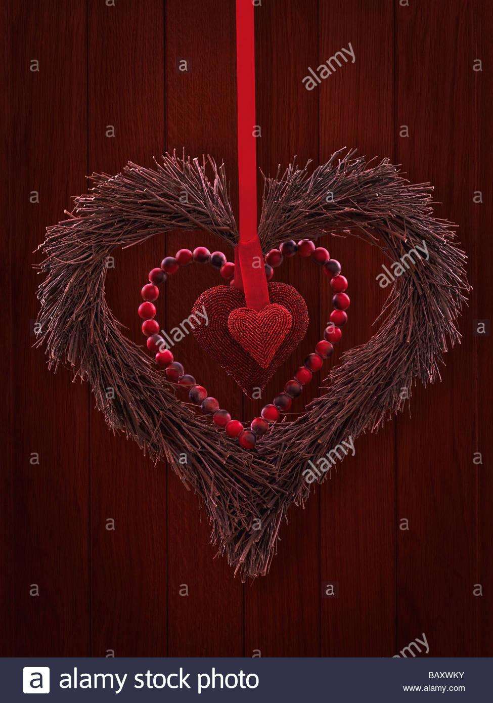 Red heart wreath hanging on door - Stock Image