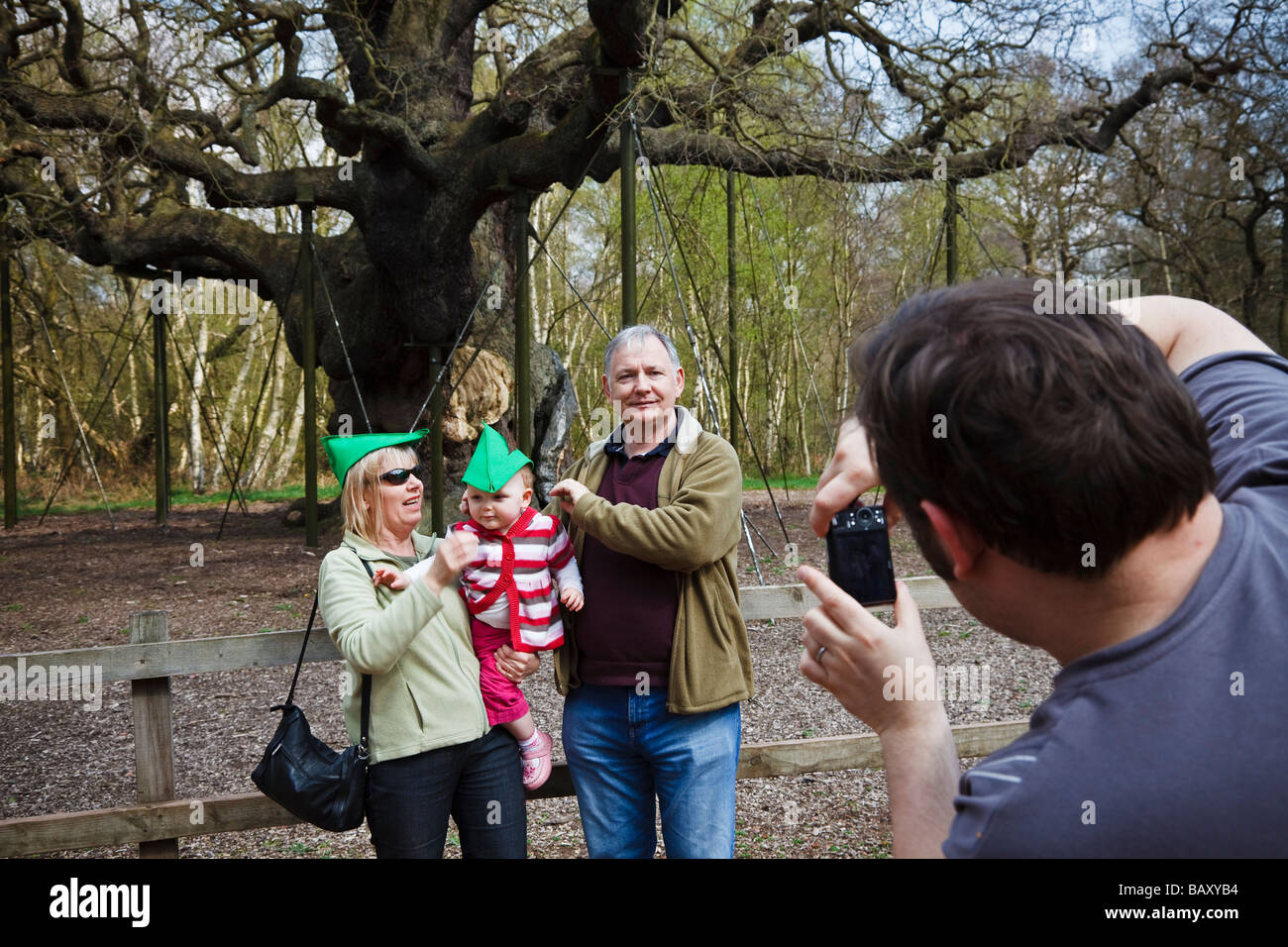 Tourists posing in 'Robin Hood' hats for a family photograph at the Major Oak, Sherwood Forest, Nottinghamshire. Stock Photo