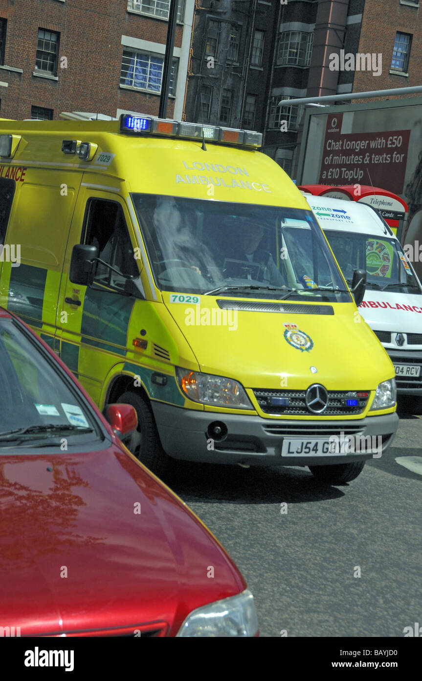 London Ambulance with blue lights flashing on the way to an emergency and stuck in traffic England UK - Stock Image