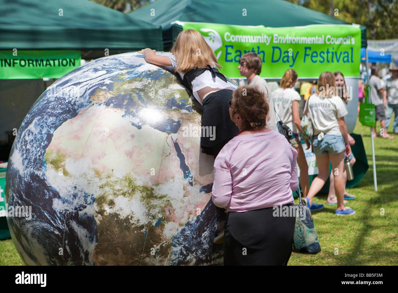 child playing with inflated world globe Earth Day Celebration Santa Barbara California United States of America - Stock Image