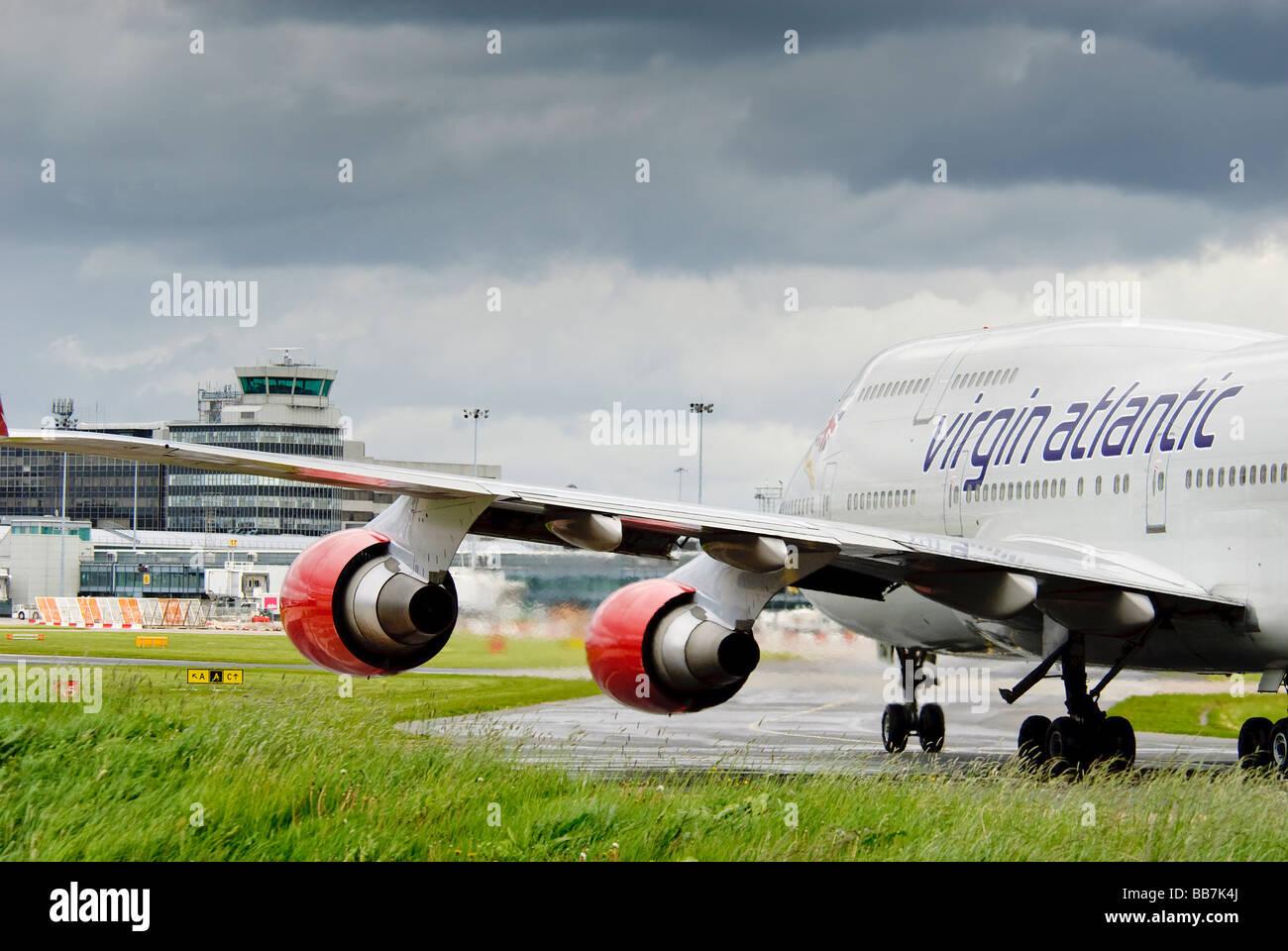 A Virgin Atlantic Jumbojet Boeing 747 taxiing at Manchester International airport towards the main terminal and - Stock Image