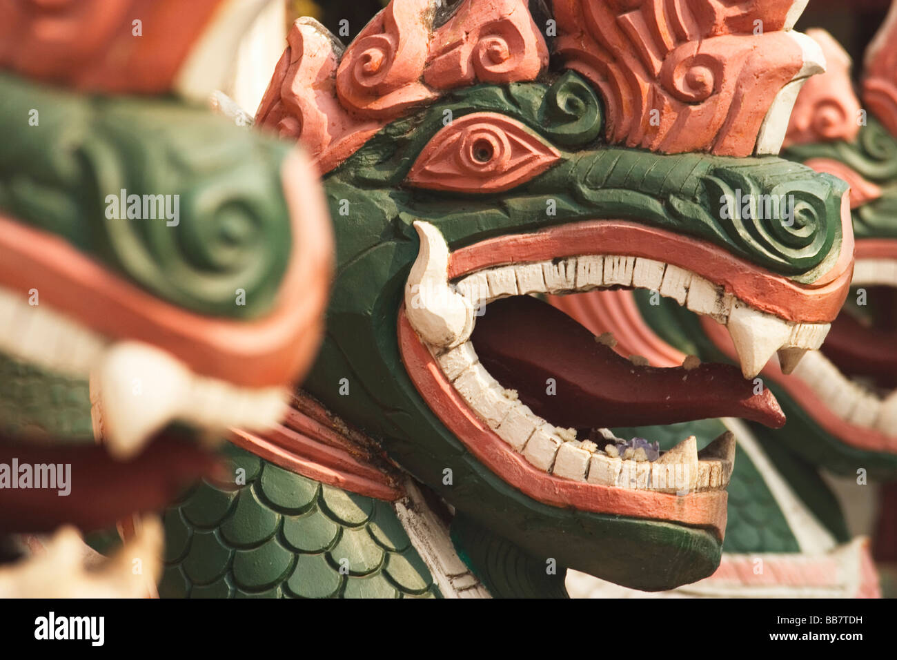 Dragon-like creatures guard the temple buildings of Wat Luang in Pakse, Lao People's Democratic Republic. - Stock Image