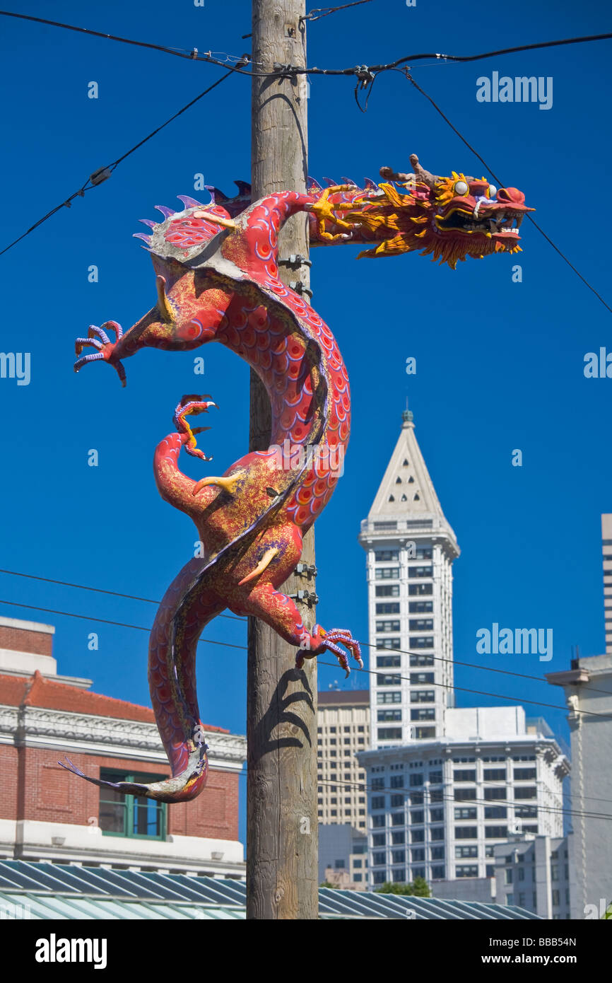 Seattle WA Pole dragon guards the International District with the Smith Tower in the background - Stock Image