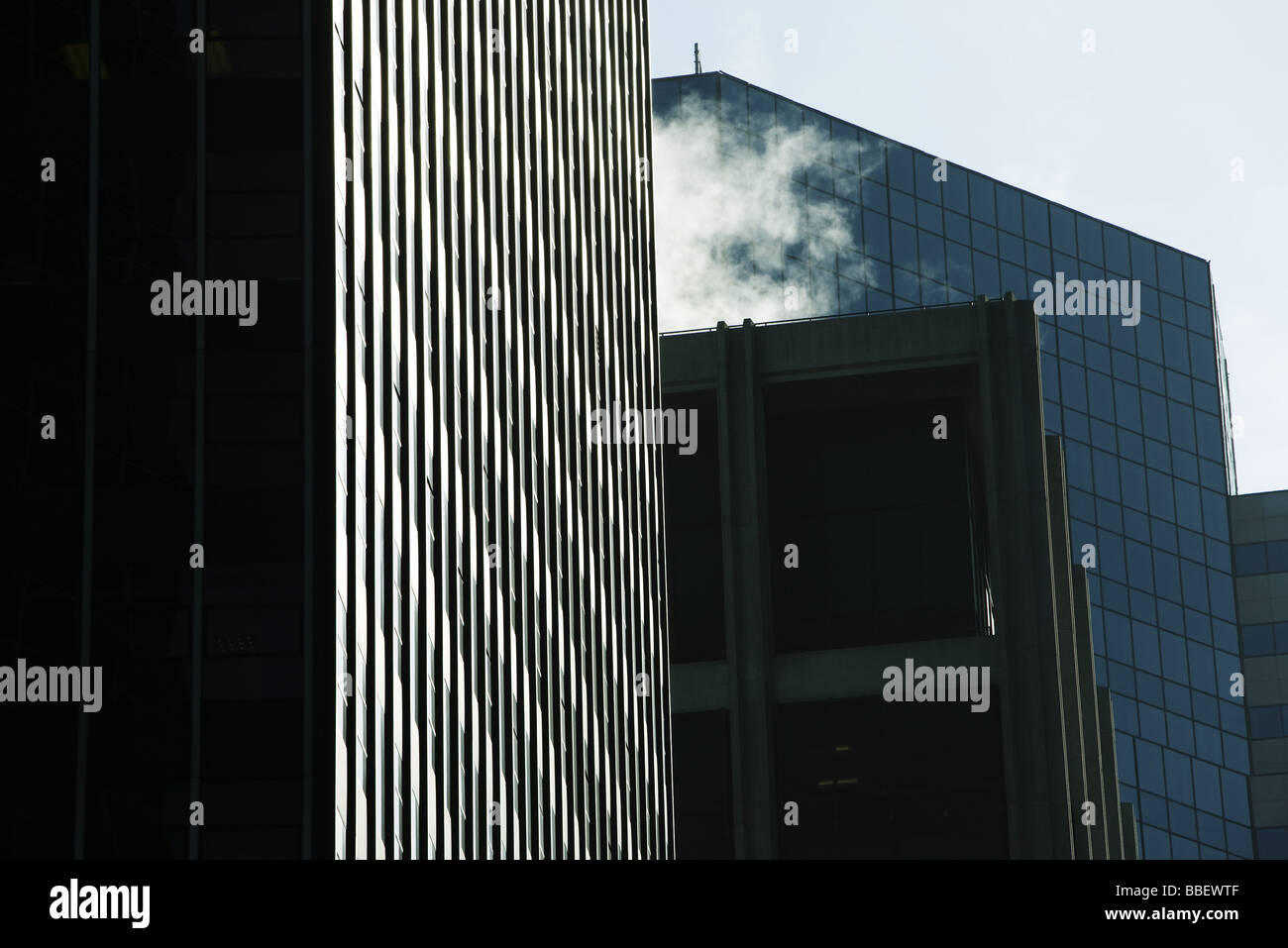 High rise office buildings side by side, steam vapor billowing from rooftop, low angle view - Stock Image
