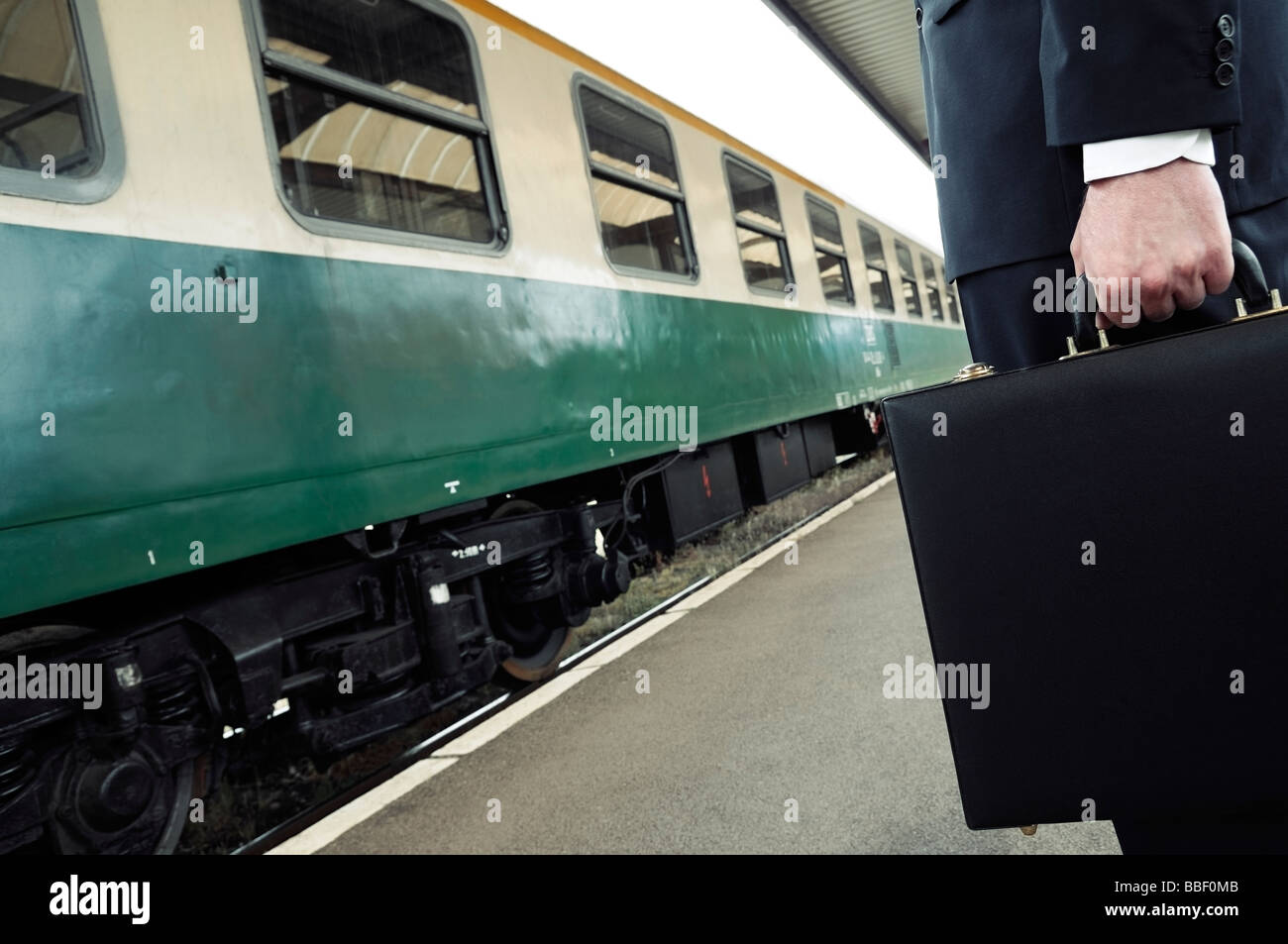 Businessman Holding a Briefcase Standing on a Train Station Platform Low Section - Stock Image