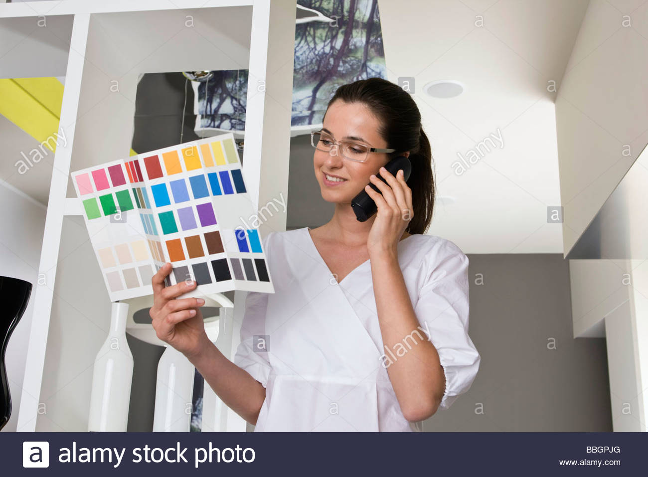 Young businesswoman on phone looking at color swatches - Stock Image