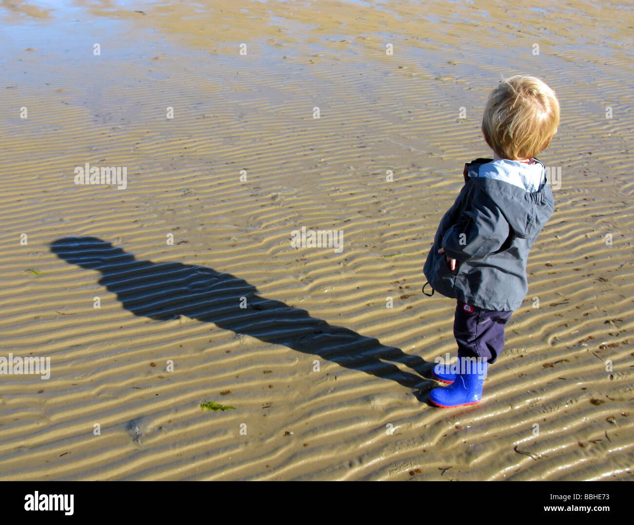 Boy alone on beach looking backwards - Stock Image