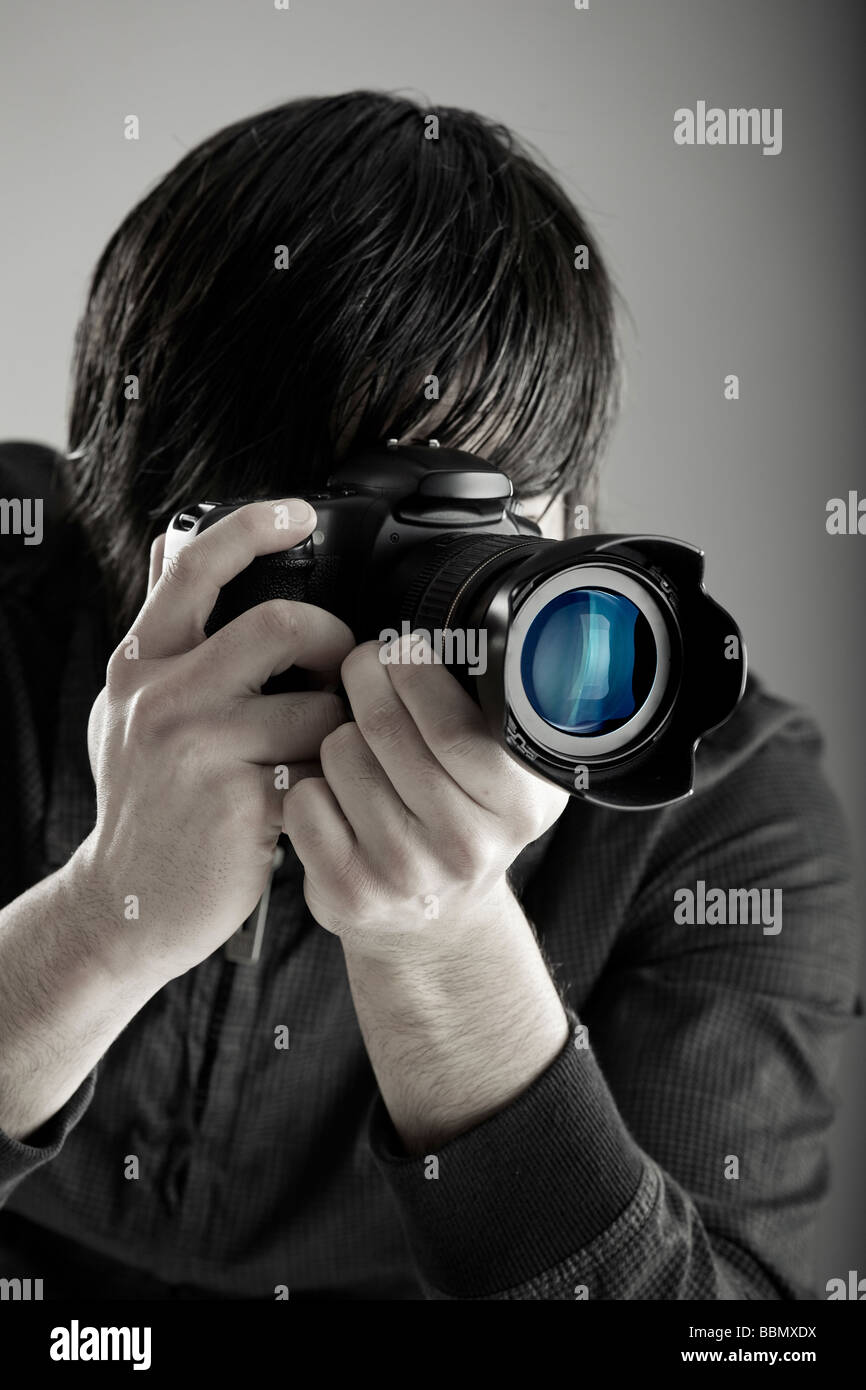 Young man holding a professional DSLR camera and taking pictures - Stock Image