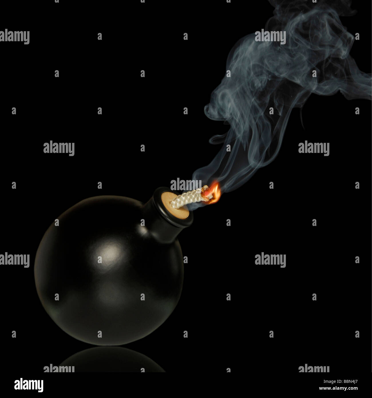 Black bomb on black, fuse is burning, symbolic symbol for danger, let the bomb explode - Stock Image
