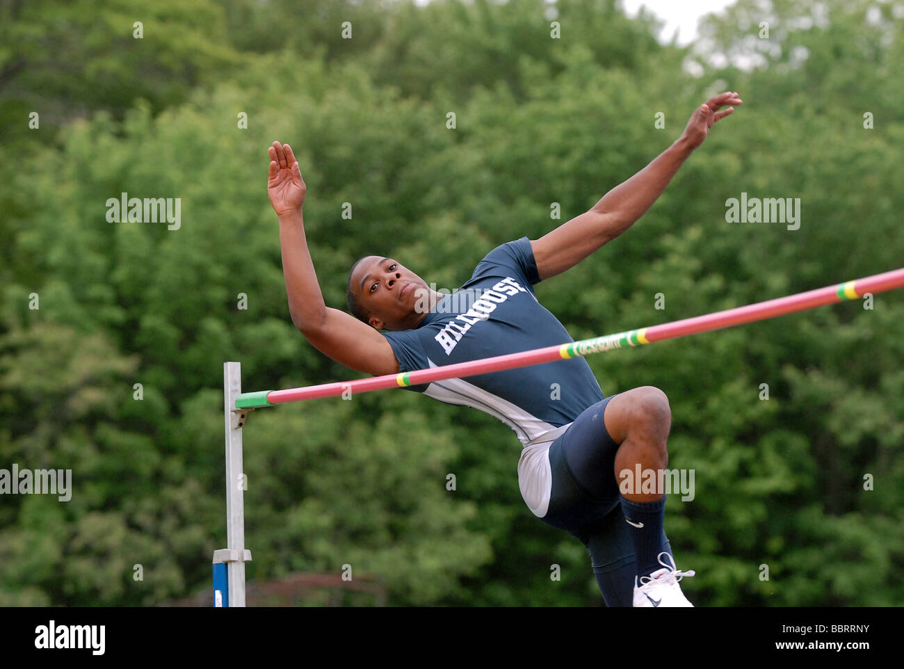 A High School track athlete jumps over the bar during the high jump during the Connecticut State Championship Track - Stock Image