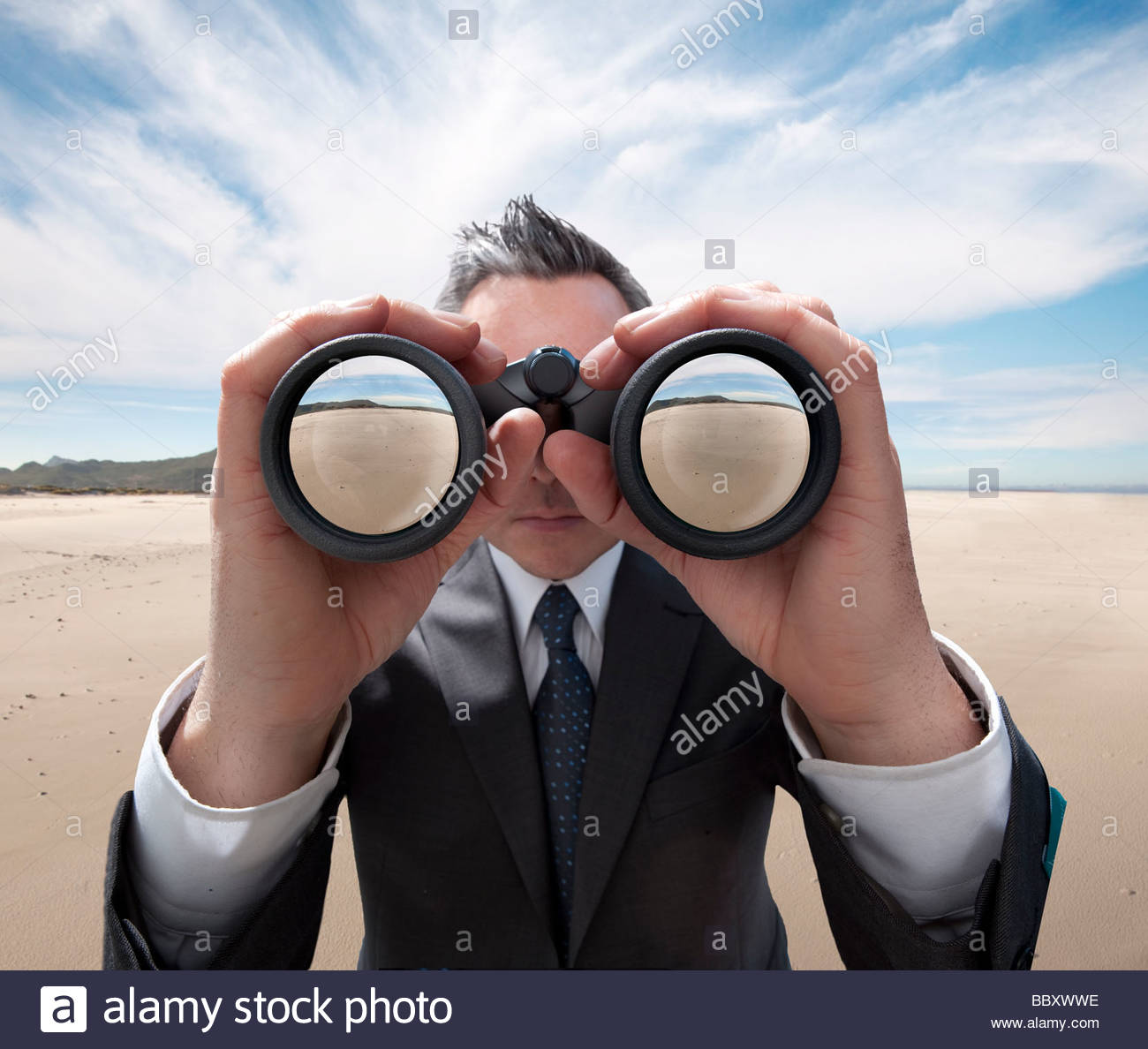 A man in a business suit standing in the desert peering through binoculars. - Stock Image
