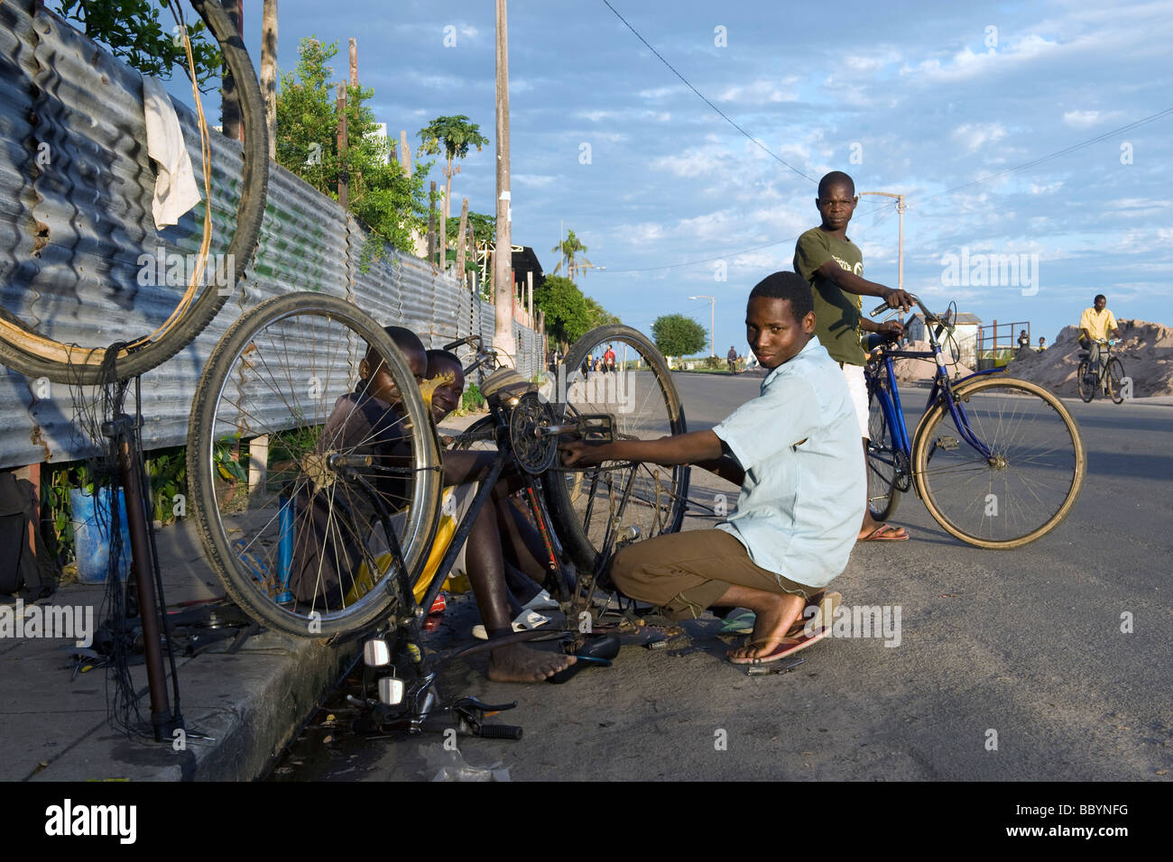 Boys running a bicycle repair workshop on the streets of Quelimane Mozambique - Stock Image