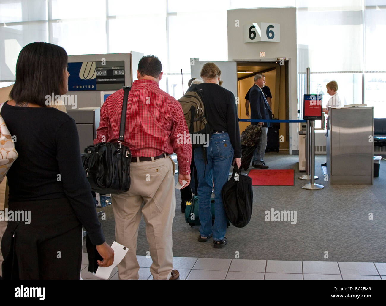 Passengers line up at airport gate to board plane Stock Photo