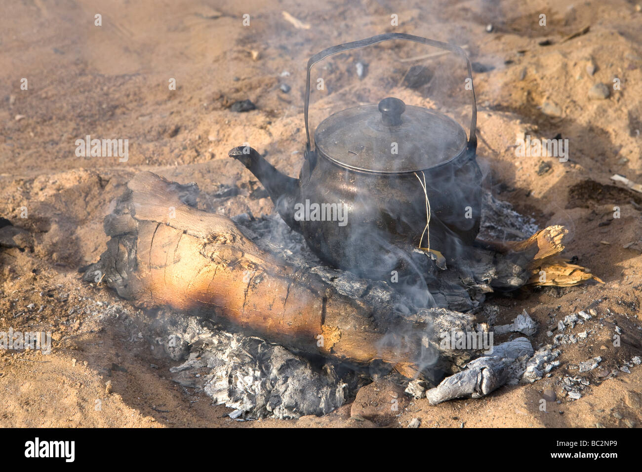 Kettle coming to boil on open fire  while camping in the Eastern Desert of Egypt, North Africa - Stock Image