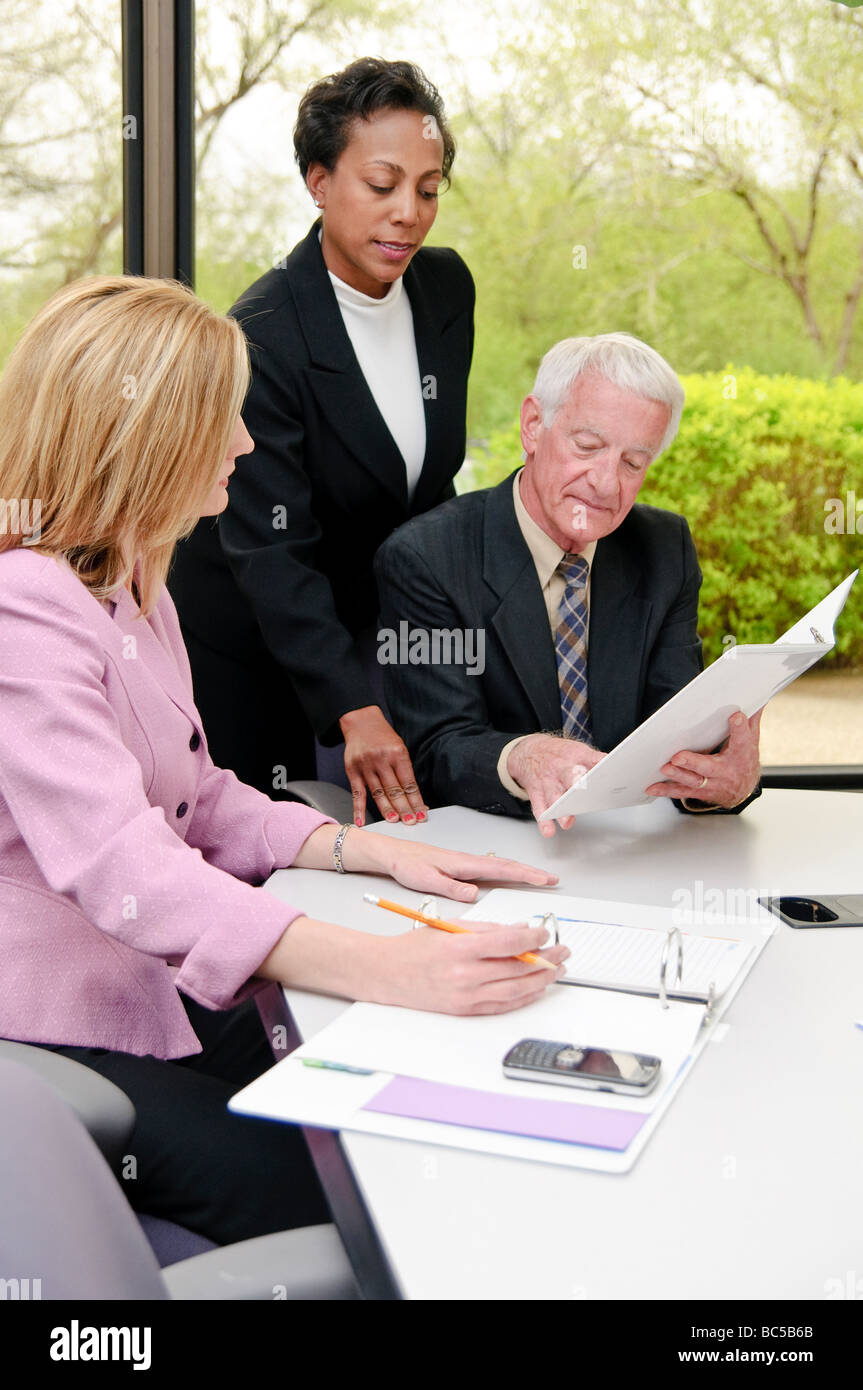 business meeting with black female, white male, and white female at a conference table - Stock Image