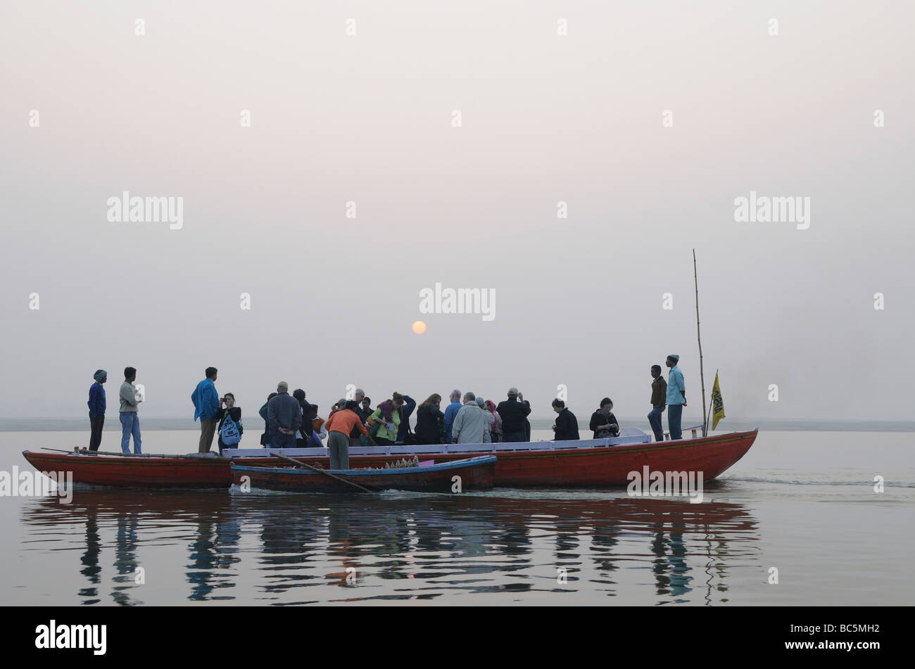 Tourists in a long rowing boat watch the sun rise over the River Ganges. Varanasi Stock Photo