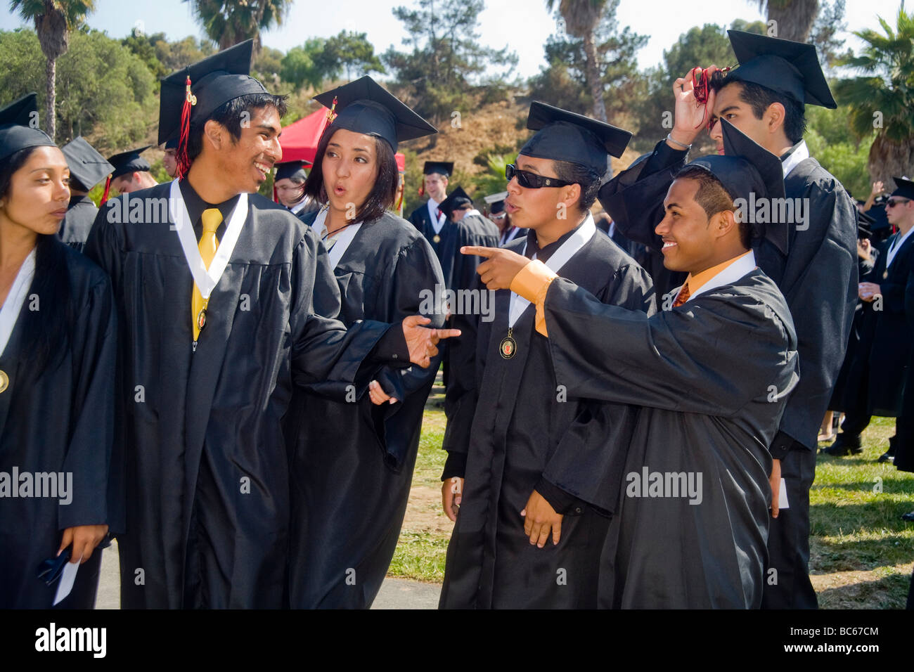 Happy Hispanic high school seniors in cap and gown enjoy each others ...