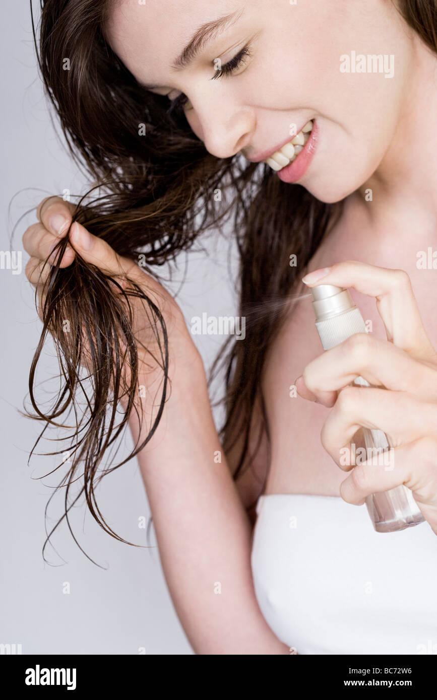 woman applying spray hair-conditioner - Stock Image