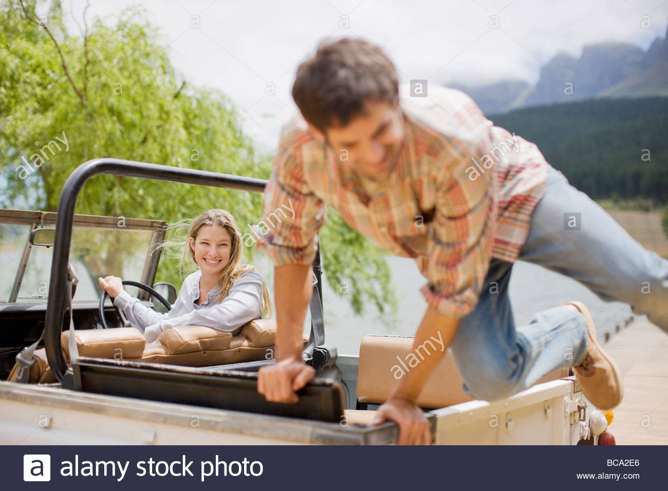 Man jumping out of back of jeep - Stock Image