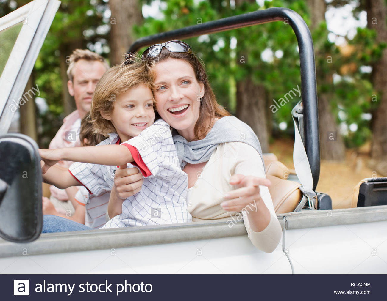 Father, mother and son riding in jeep - Stock Image