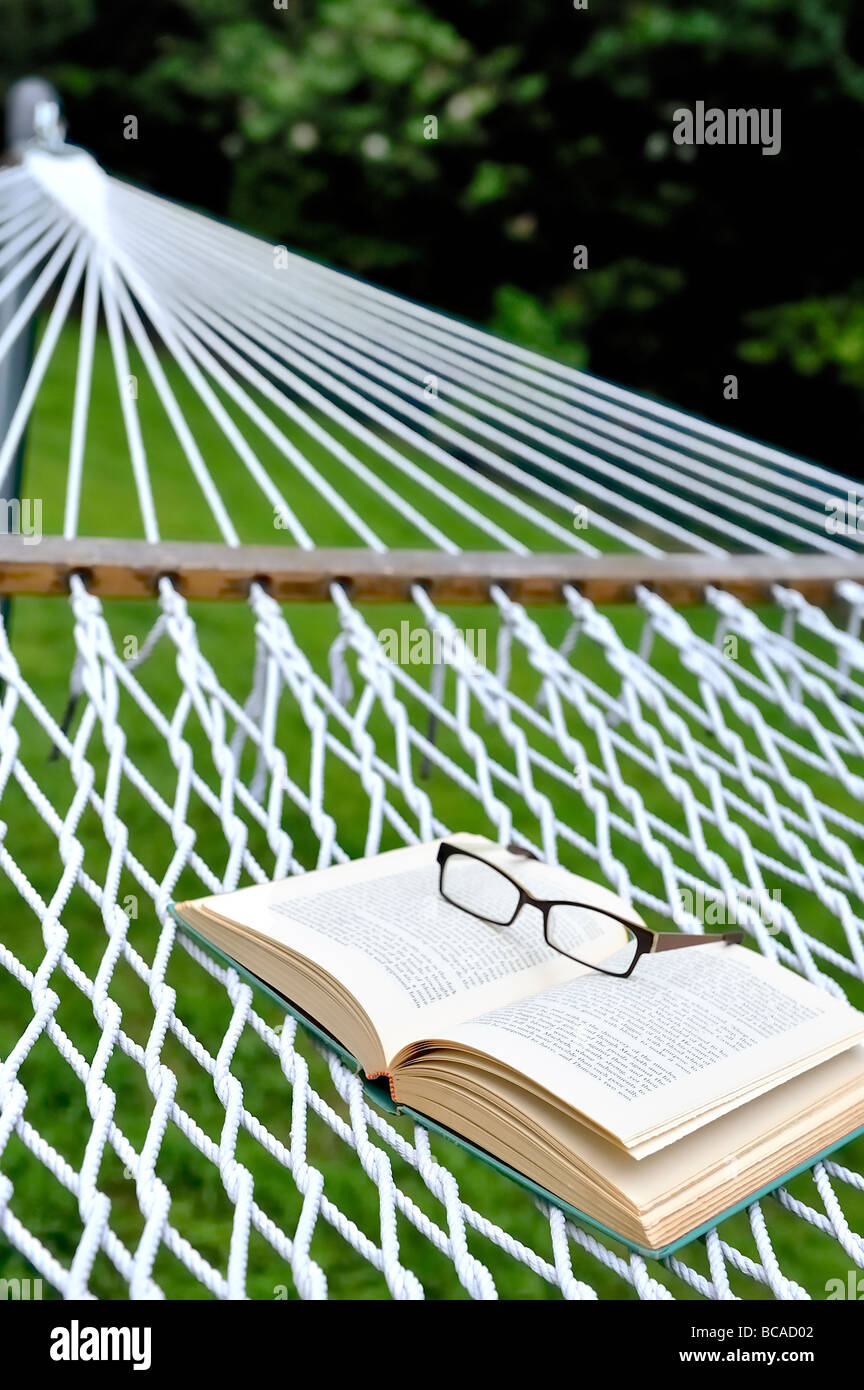 Summer reading staycation home vacation retirement weekend concept glasses eyeglasses spectacles open book backyard Stock Photo