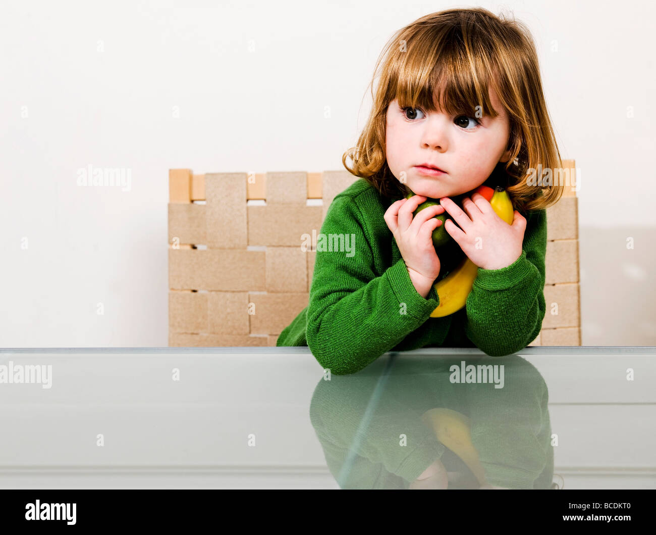 young girl with holding fruit in arms - Stock Image