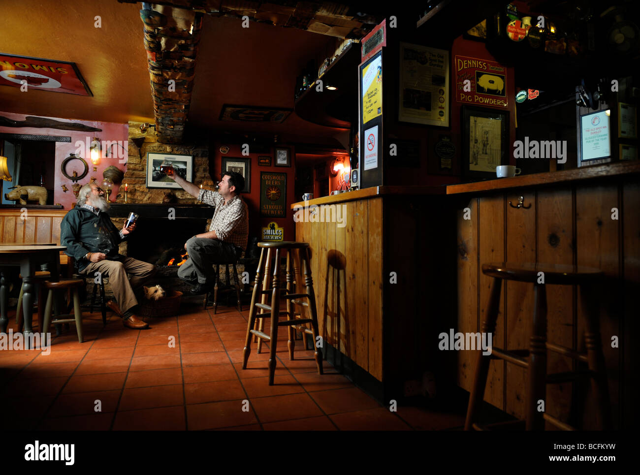 TWO MEN CHATTING BY AN OPEN FIRE IN A TRADITIONAL PUB GLOUCESTERSHIRE ENGLAND UK Stock Photo