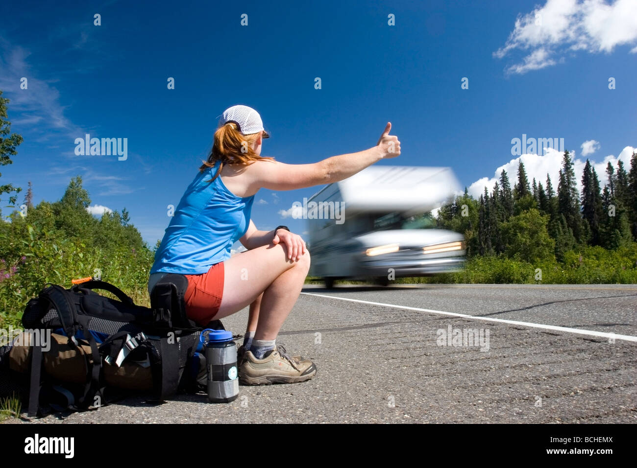 Female backpacker tries to hitch a ride on the Parks Highway in Denali State Park Interior Alaska summer - Stock Image