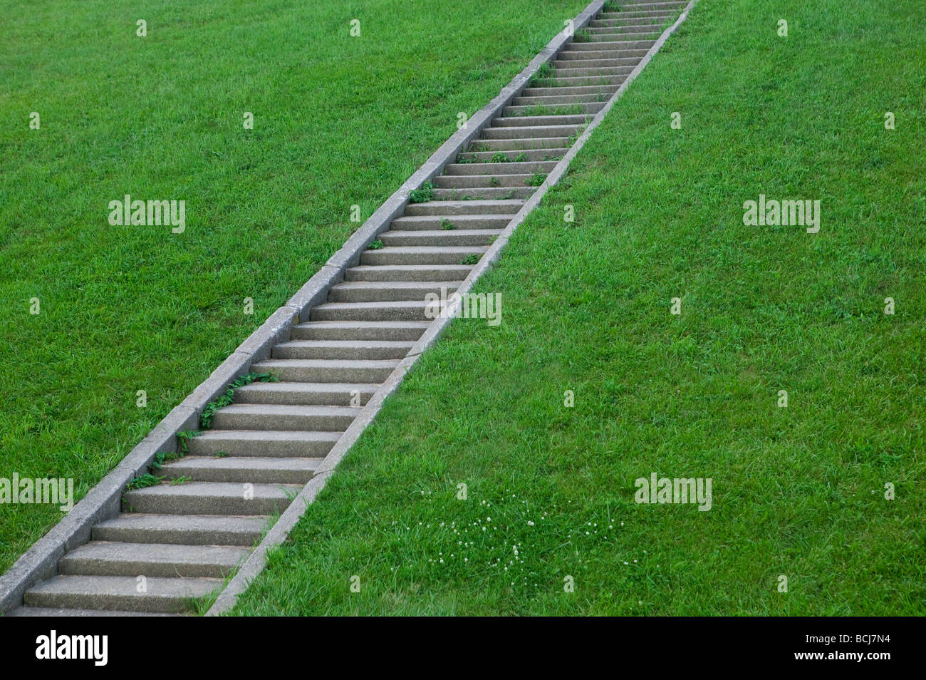 Diagonal pattern of concrete steps on grass covered hillside - Stock Image