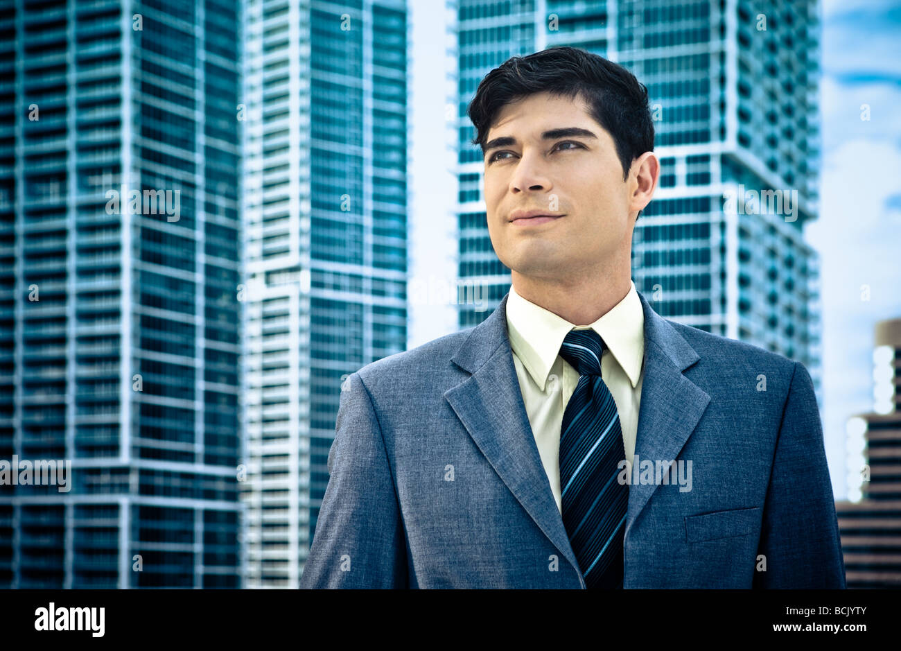 Confident Latin businessman with architectural backdrop - Stock Image