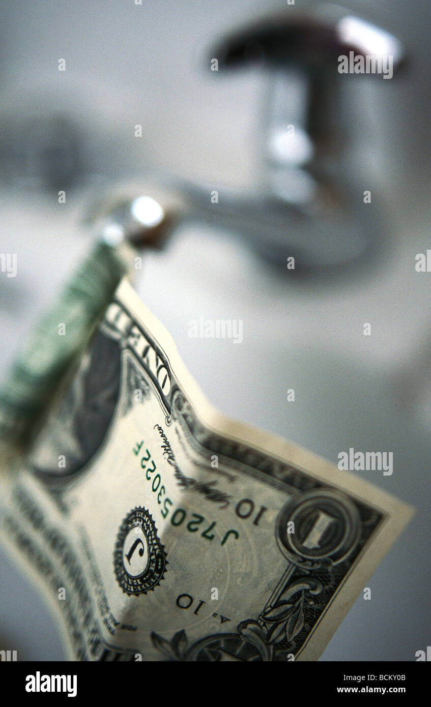 Dollar bill coming out of faucet - Stock Image