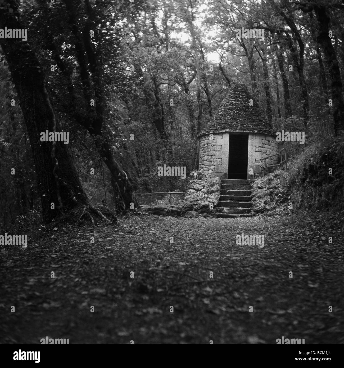 Small stone building in woods, black and white - Stock Image