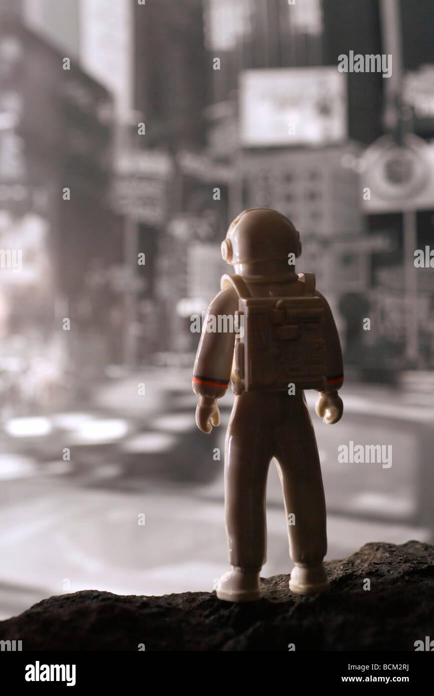 Plastic astronaut contemplating urban scene, rear view - Stock Image