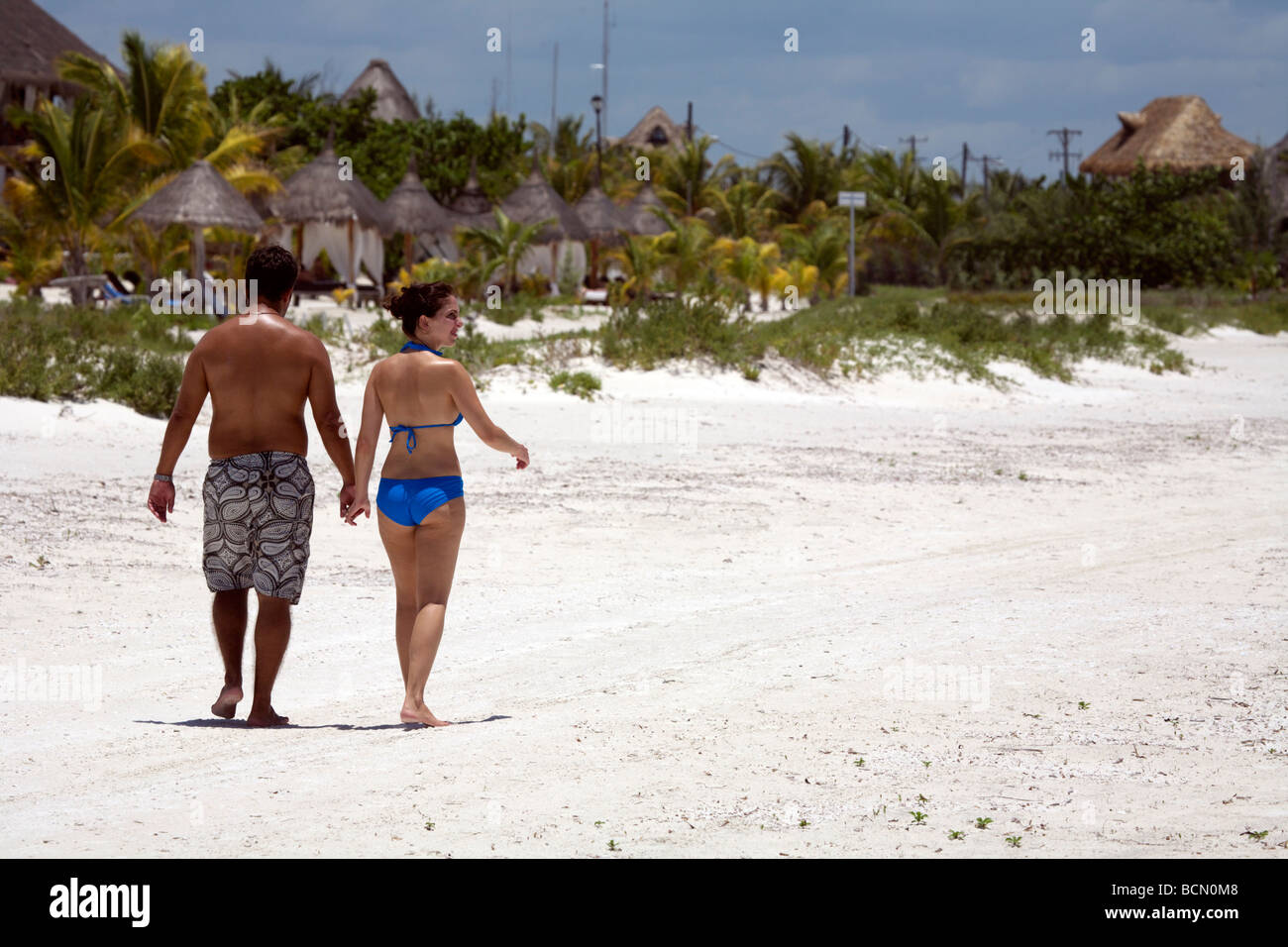 Young couple walking hand in hand on the white sands of Holbox Island, Quintana Roo, Yucatán Peninsula, Mexico, - Stock Image