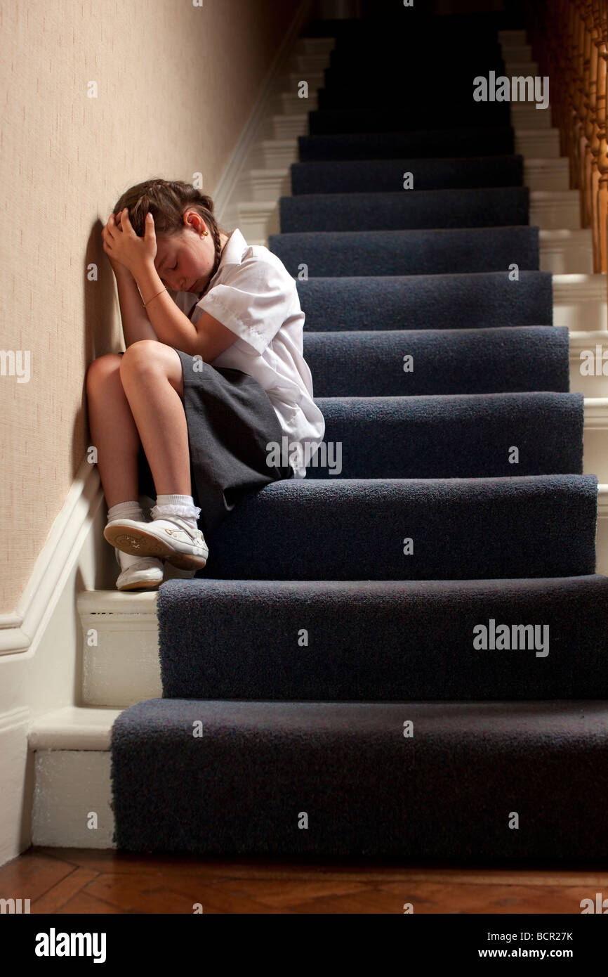 Girl sat alone on stairs - Stock Image