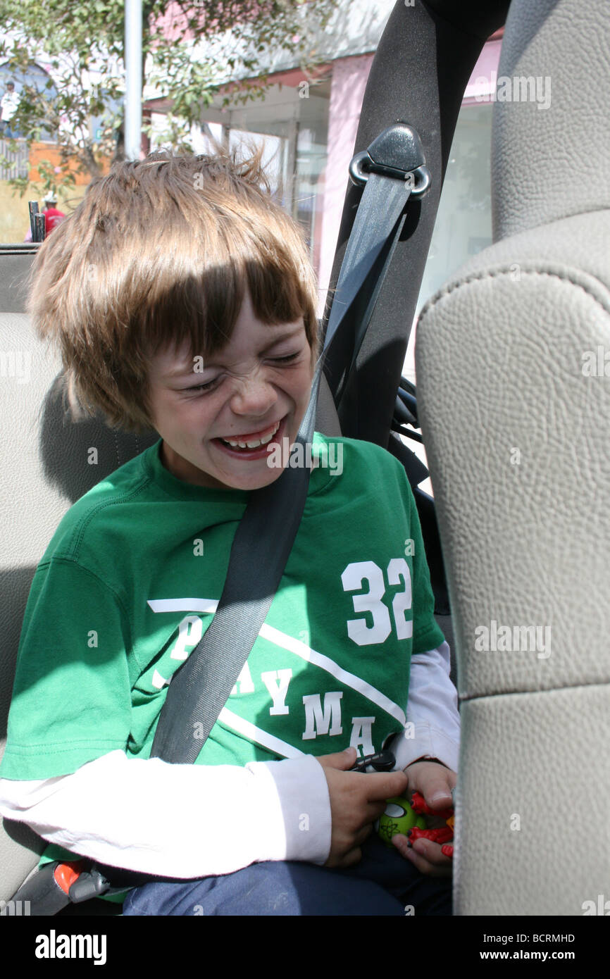 seven year old boy laughing hysterically in the back seat of a jeep - Stock Image