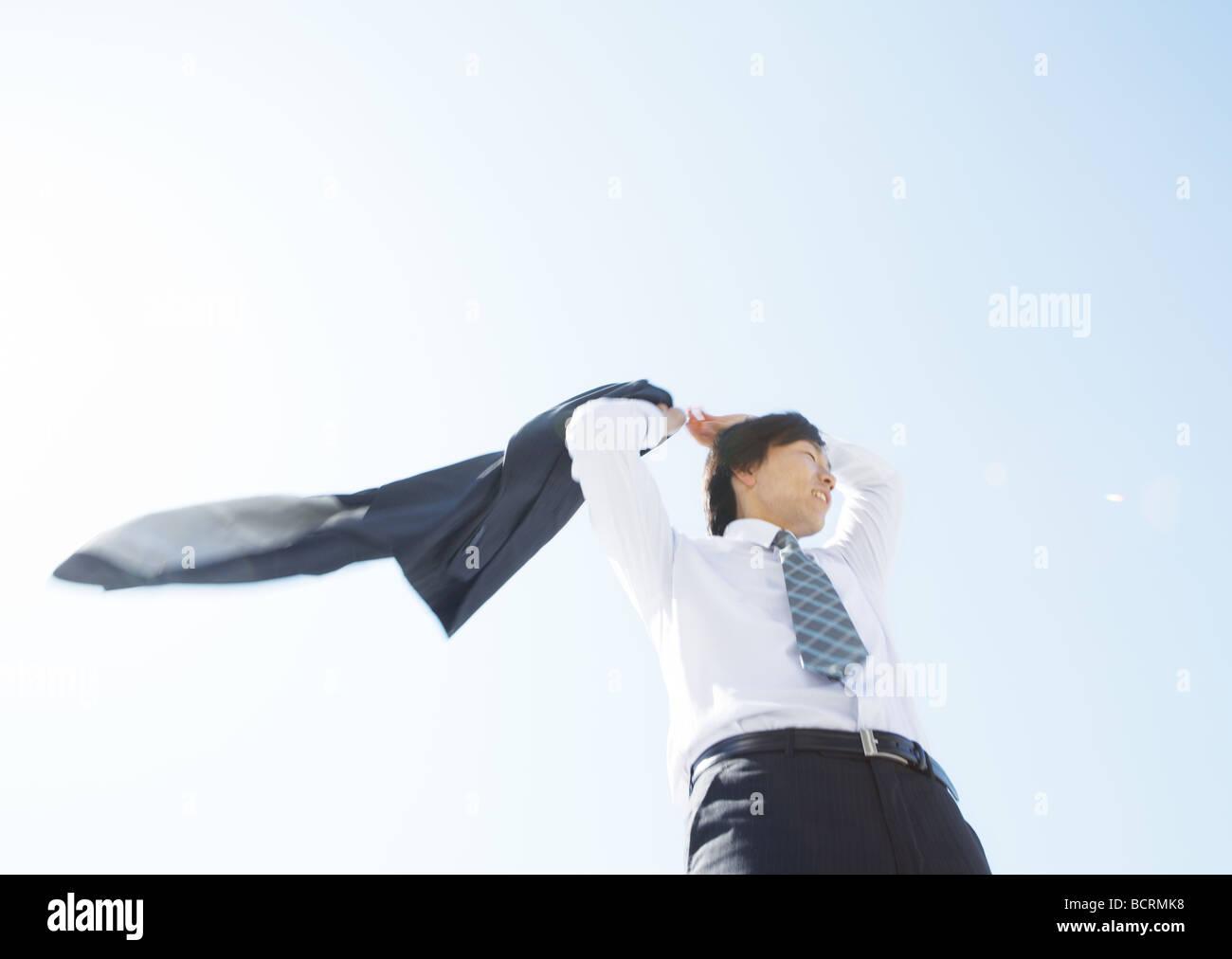 Businessman taking off his jacket - Stock Image