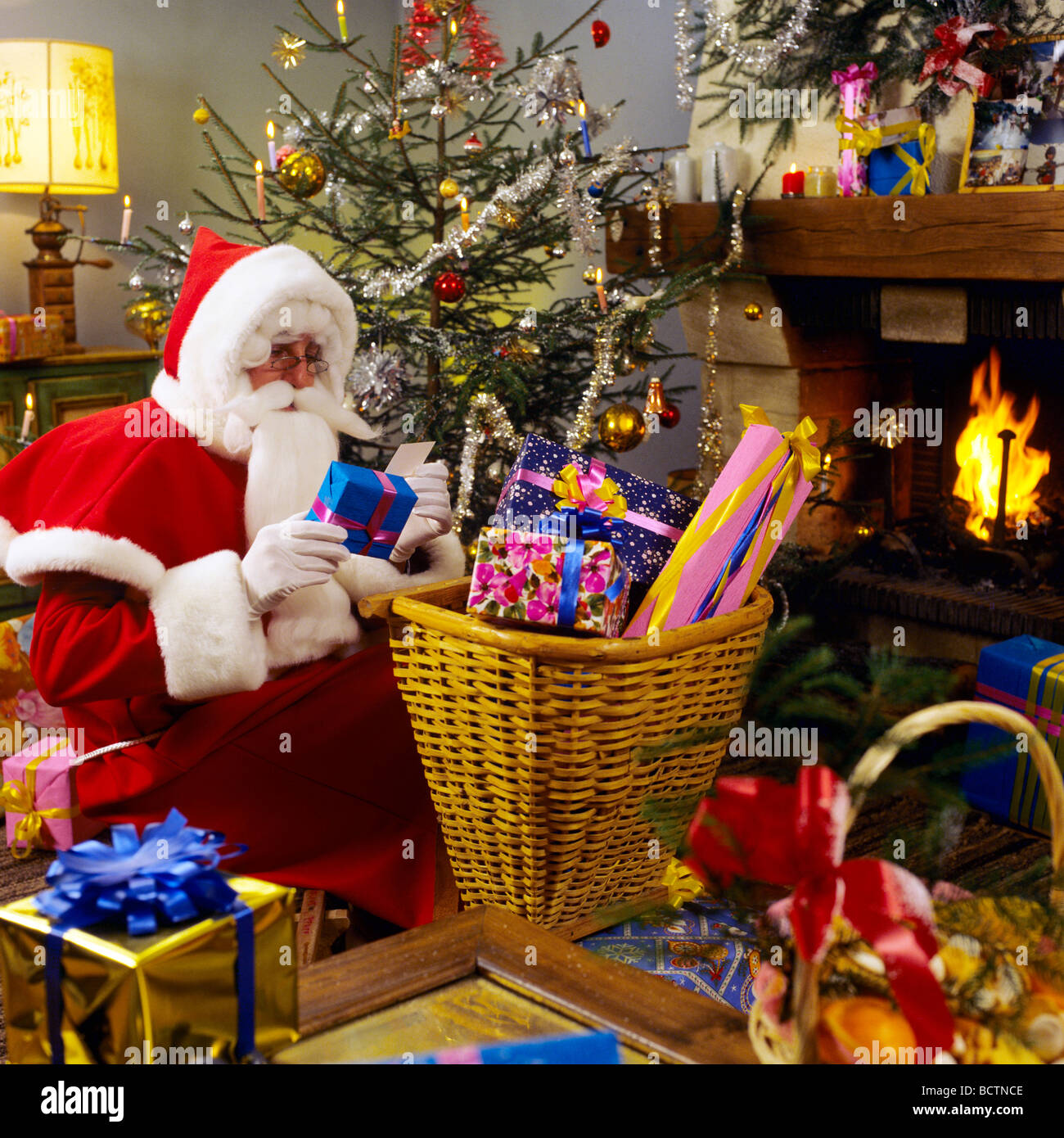 mr santa claus preparing christmas presents under the tree - Santa Claus Presents