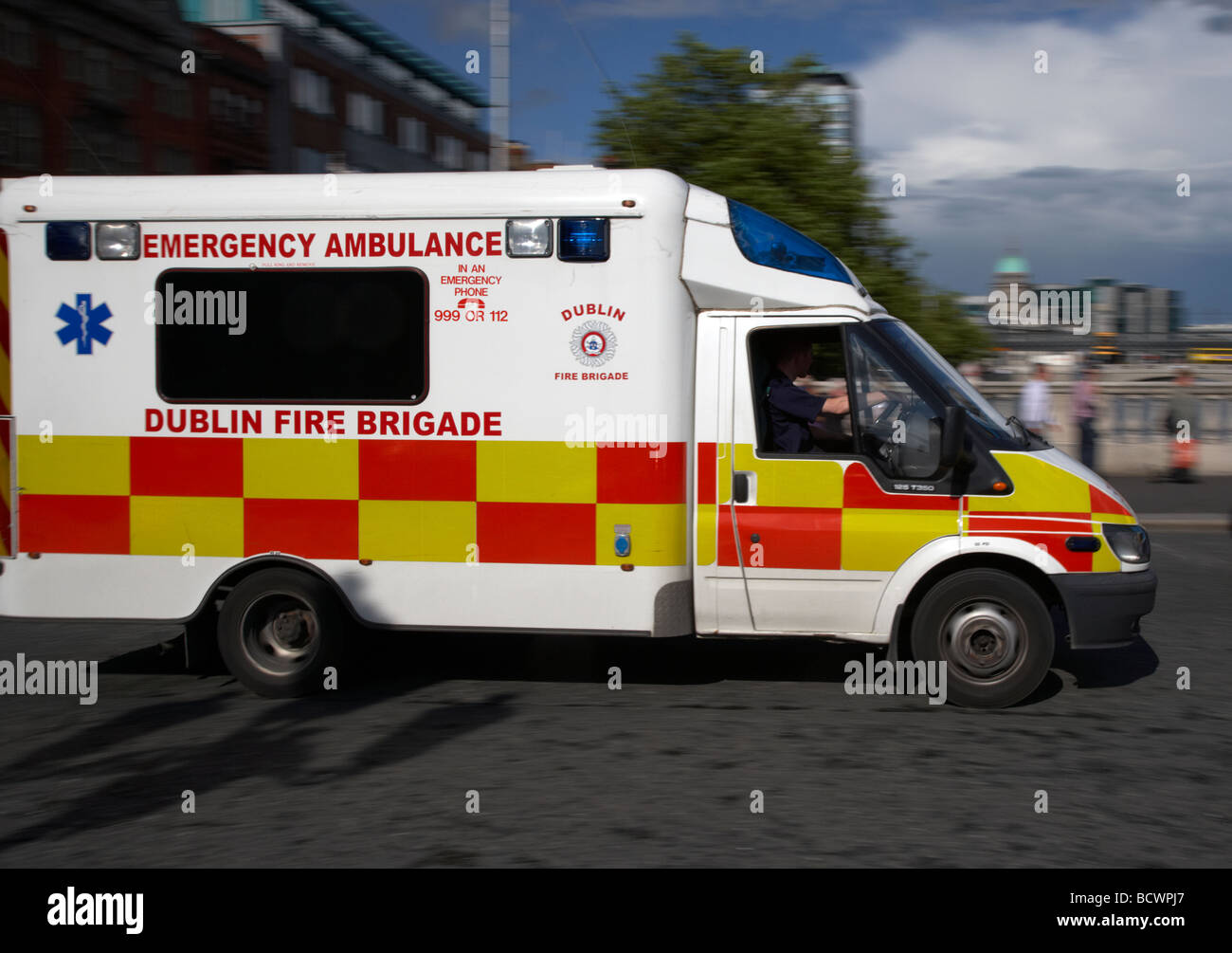 emergency ambulance from the dublin fire brigade rushing through dublin city centre republic of ireland - Stock Image