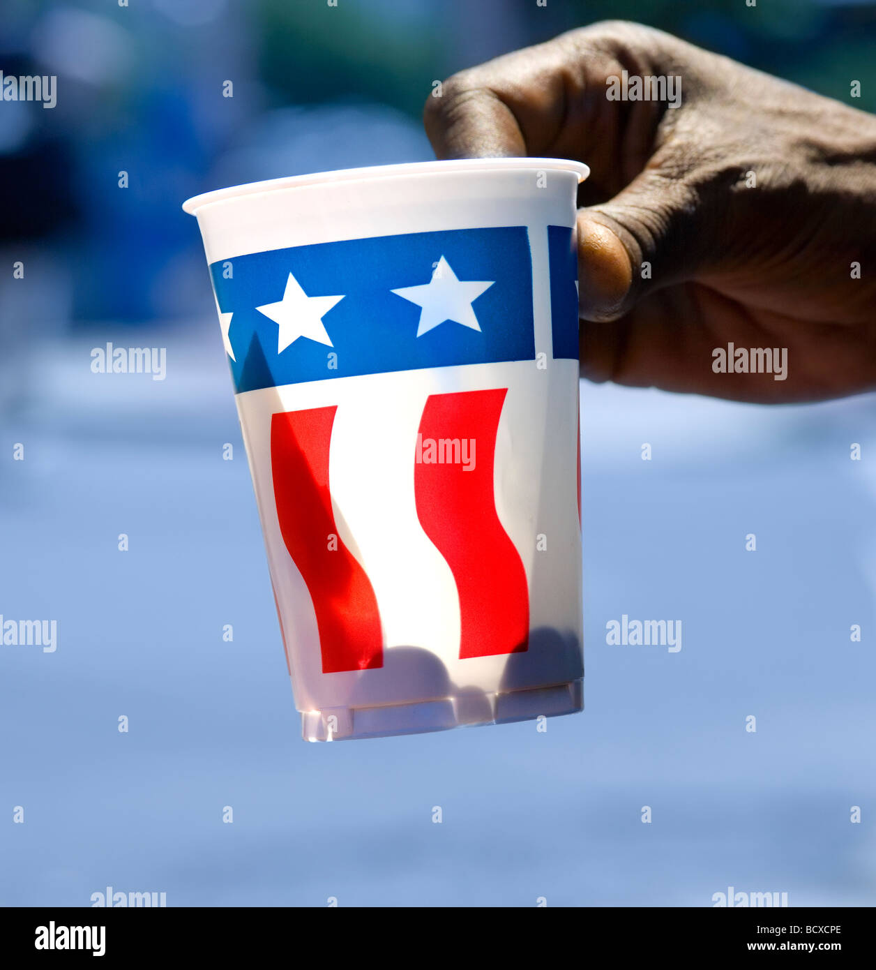 https://c7.alamy.com/comp/BCXCPE/hand-of-homeless-person-holding-out-paper-cup-with-us-flag-begging-BCXCPE.jpg