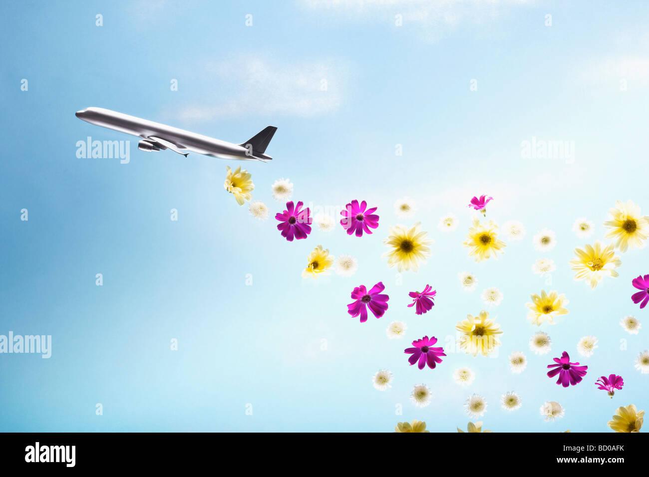 A plane emitting flowers - Stock Image