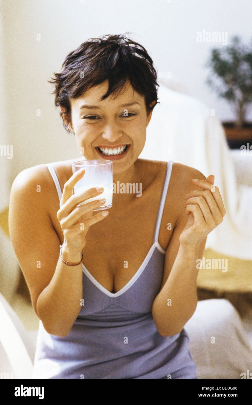 Woman smiling, holding glass of milk - Stock Image