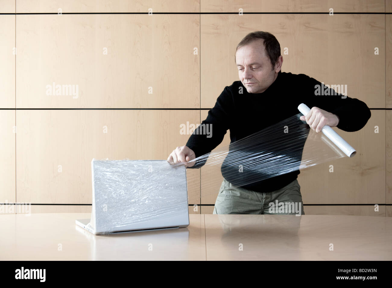Man wrapping computer with plastic film - Stock Image