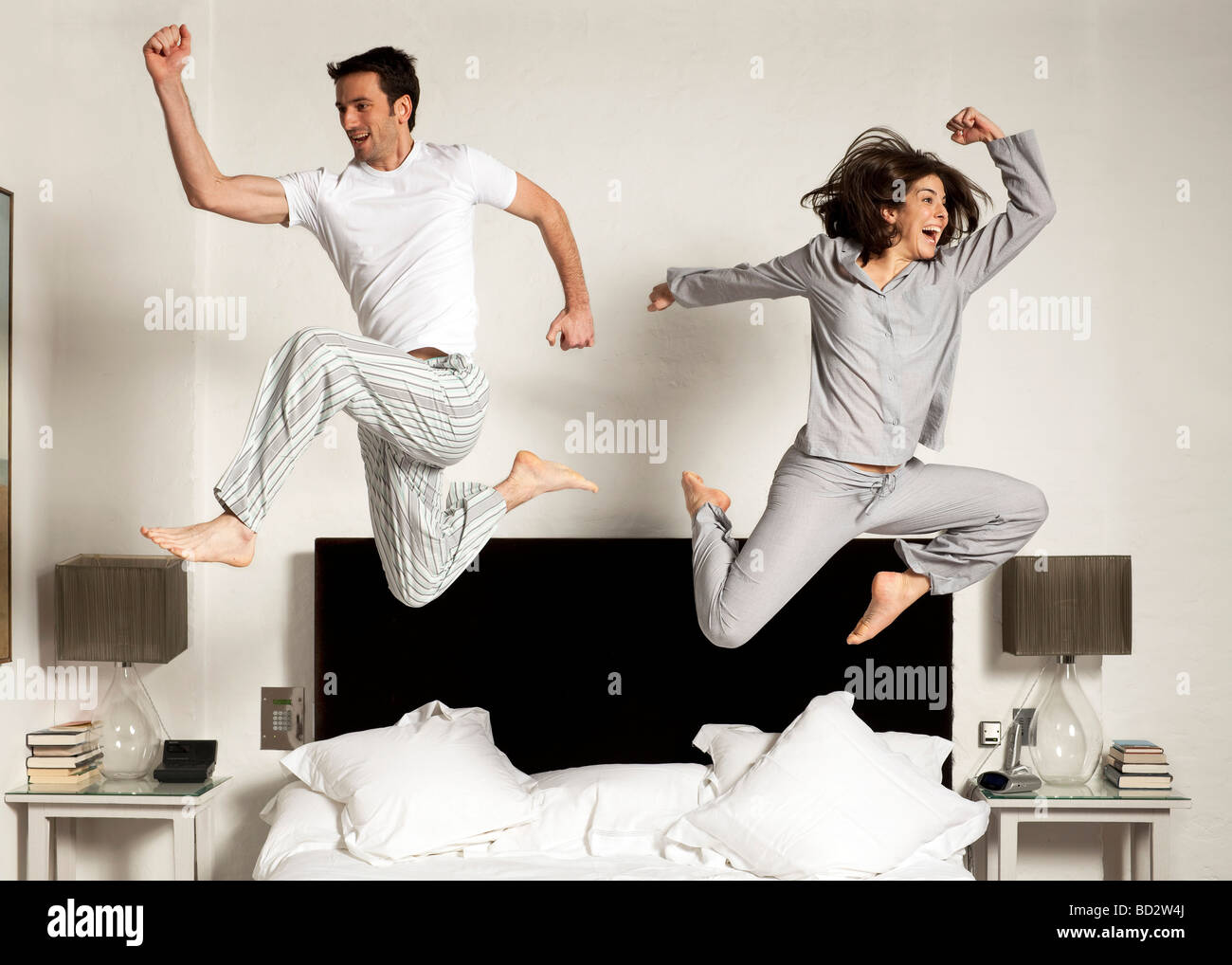 couple leaping out of bed Stock Photo