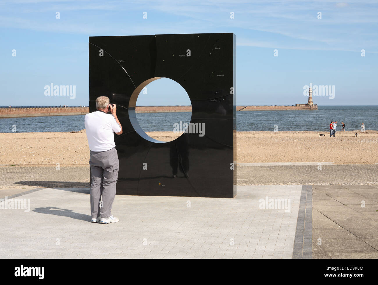man-taking-a-photograph-of-roker-lightho